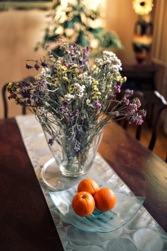 kitchen table with white table runner with a clear vase of flowers and a bowl of oranges