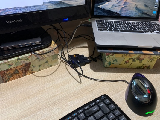 photo of a USB hub connected to a laptop, mouse, and keyboard. The laptop and the monitor sit on boxes to raise them to an ergonomic height.